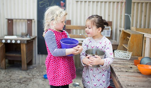 Two children playing with buckets